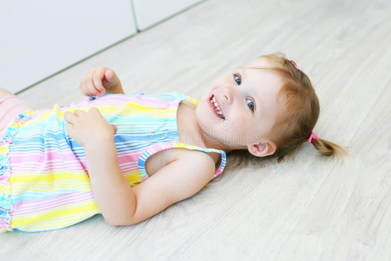 Vrolijk leuk meisje die op de vloer in de kinderen ` s liggen stock foto's