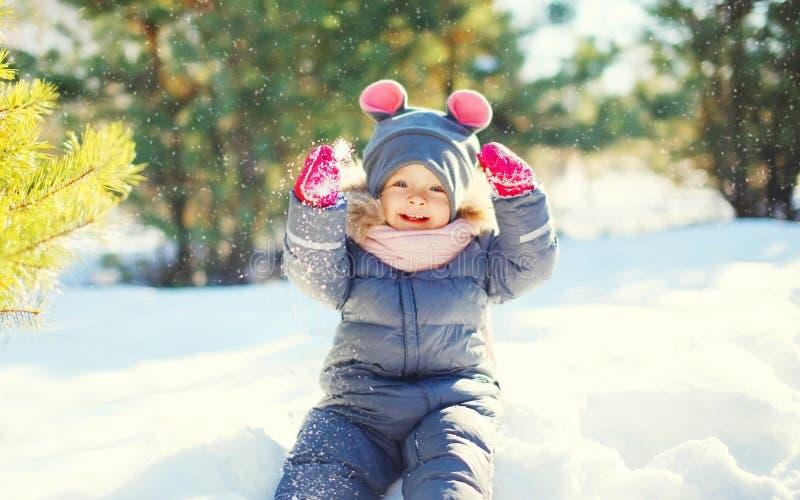 Vrolijk leuk weinig kind die op sneeuw in de winter spelen royalty-vrije stock foto's