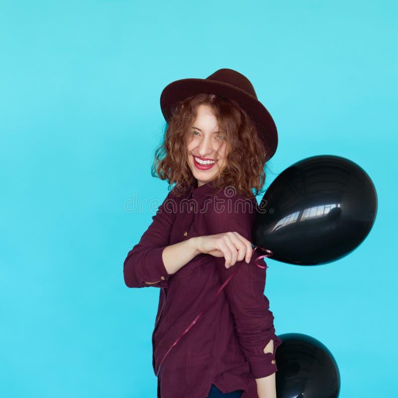 Vrolijk maniermeisje die met zwarte ballons dansen stock fotografie