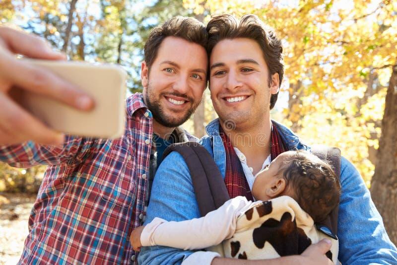 Vrolijk Mannelijk Paar met Baby die Selfie op Gang in Bos nemen royalty-vrije stock afbeeldingen