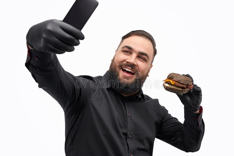 Vrolijk mannetje die selfie met hamburger nemen stock afbeeldingen