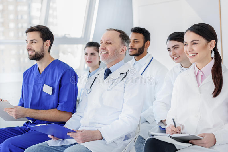 Vrolijk medisch team die aan nieuwe informatie luisteren stock fotografie