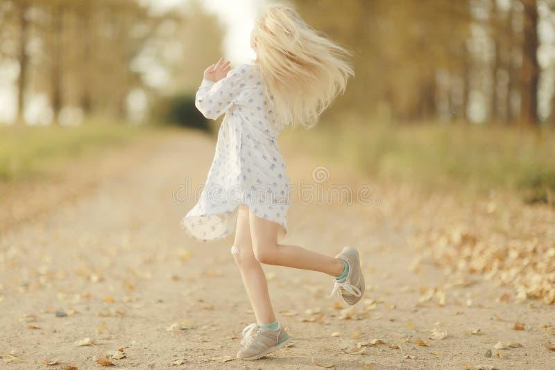 Vrolijk meisje bij de herfstweg stock afbeeldingen