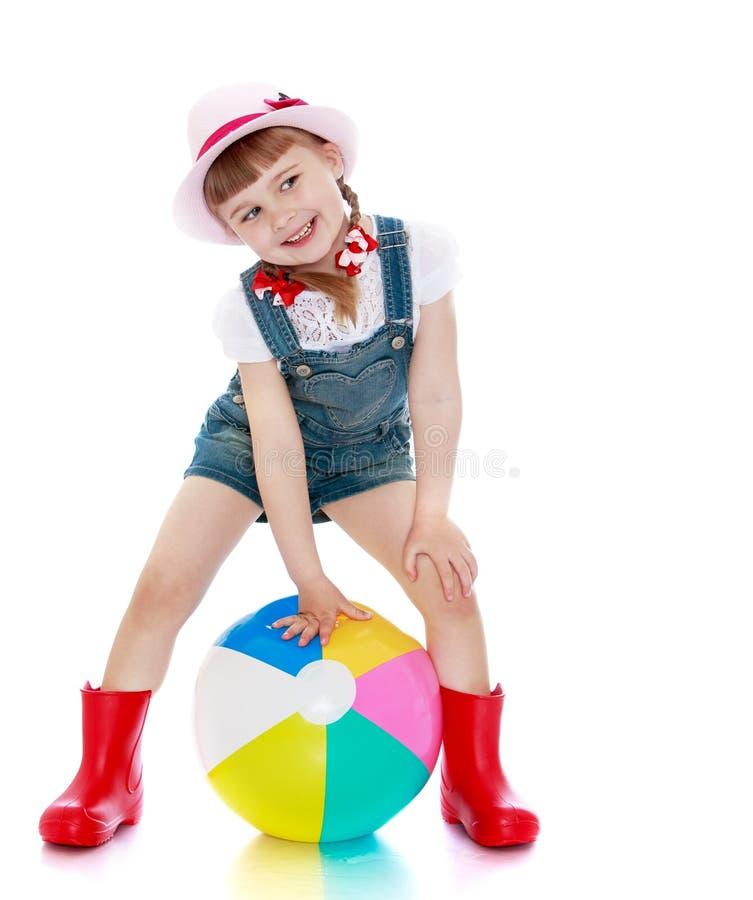 Vrolijk meisje in borrels, hoed en rubberlaarzen royalty-vrije stock afbeeldingen