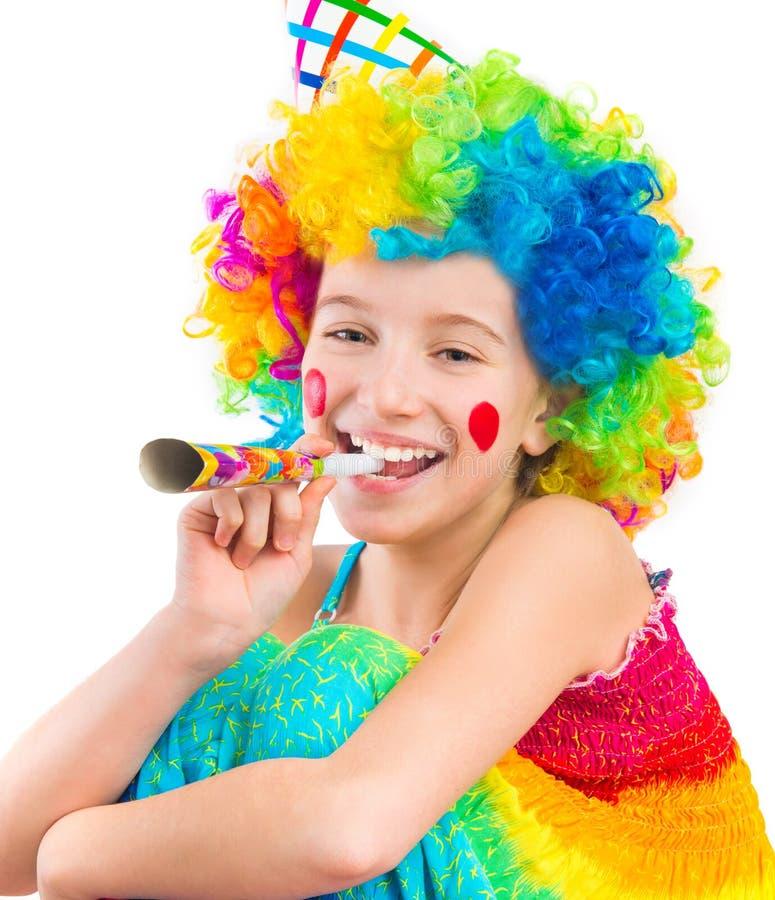 Vrolijk meisje in de krullende clownpruik en ventilator van de partijhoorn royalty-vrije stock afbeelding