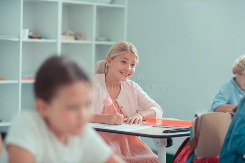 Vrolijk meisje die aan haar leraar tijdens de test glimlachen royalty-vrije stock foto's