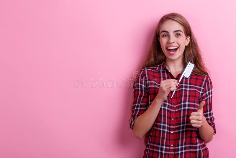 Vrolijk meisje die een document tandenborstel houden en duim tonen Ei op toilet Roze achtergrond royalty-vrije stock afbeelding