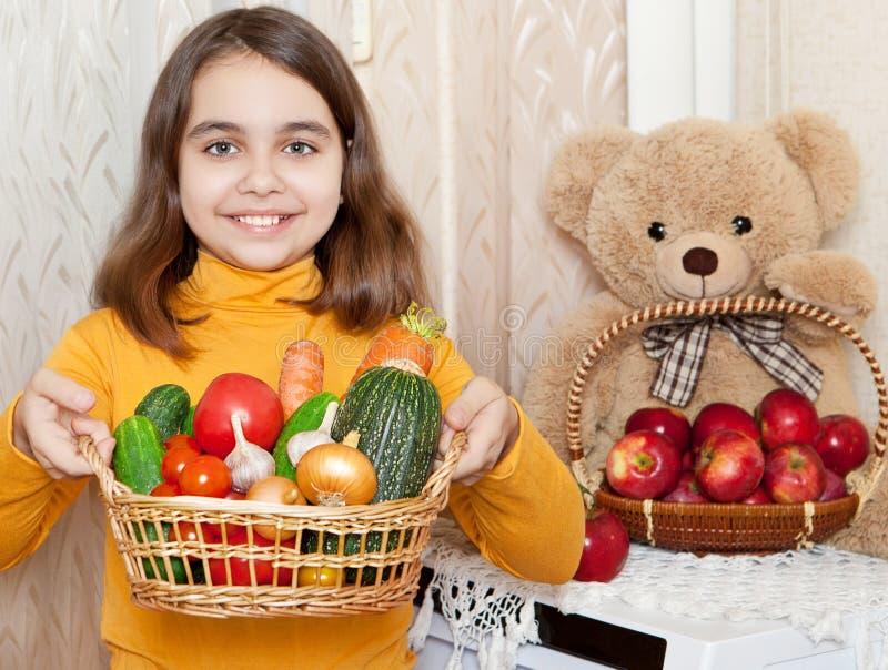 Vrolijk meisje die een mand van groenten houden stock fotografie