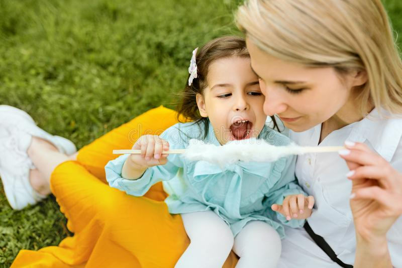 Vrolijk meisje die gesponnen suiker met haar mamma eten, die op het groene gras in het park zitten stock foto
