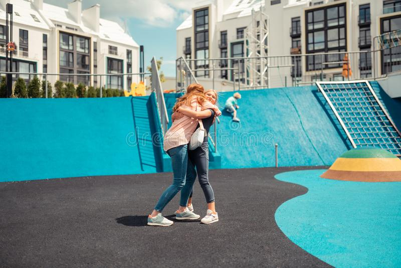 Vrolijk meisje die haar mum vast op een sportengrond koesteren royalty-vrije stock fotografie