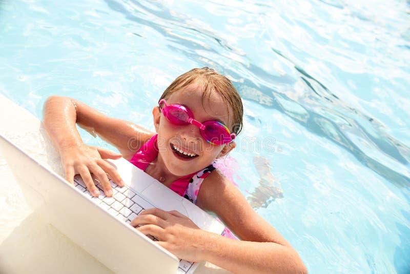Vrolijk meisje die laptop in zwembad met behulp van stock fotografie