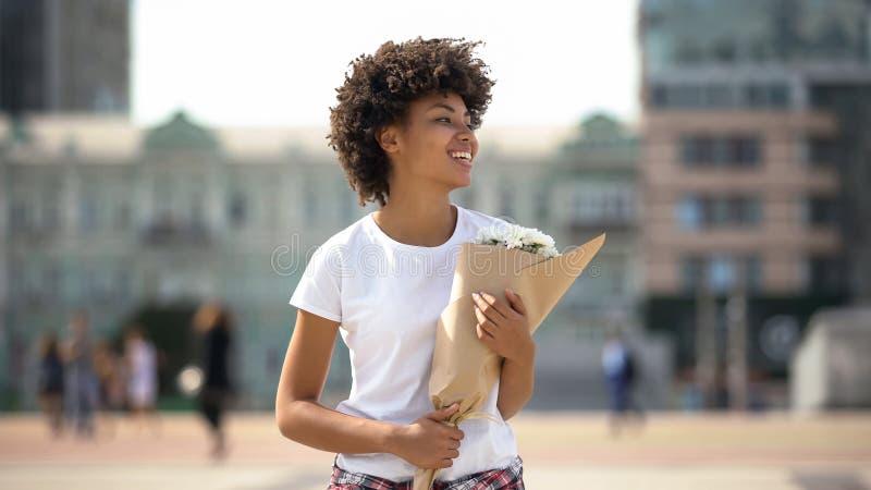Vrolijk meisje die met boeket van bloemen, heden van vriend, geluk glimlachen royalty-vrije stock foto's