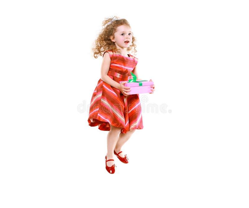 Vrolijk meisje die met een gift springen stock afbeelding