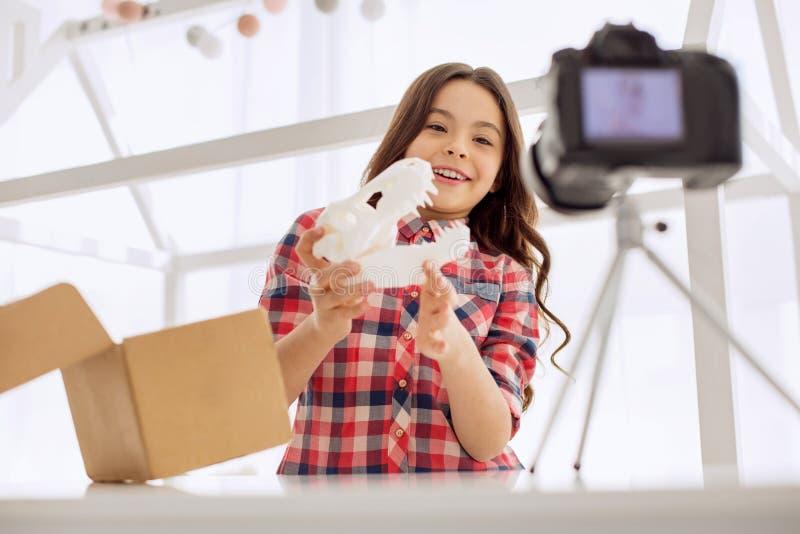 Vrolijk meisje die nieuw stuk speelgoed in het unboxing van video tonen stock afbeeldingen