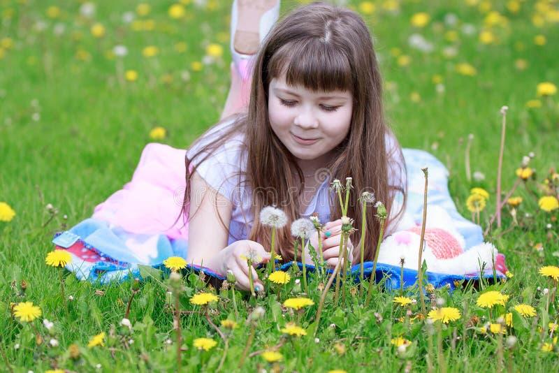 Vrolijk meisje die op een mooie sprei in het gras liggen stock afbeeldingen