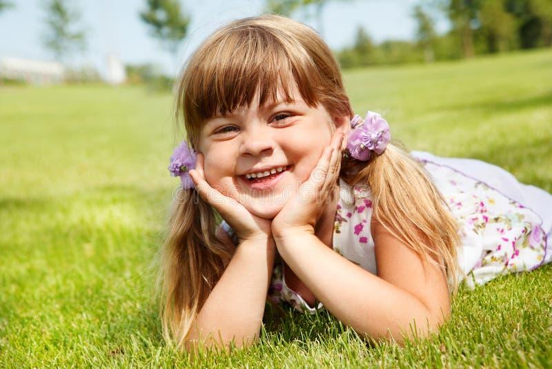 Vrolijk meisje die in de zomer liggen stock fotografie