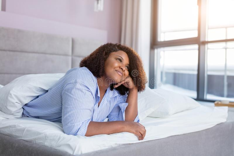 Vrolijk meisje die over haar vriend denken terwijl het rusten in het comfortabele bed royalty-vrije stock afbeelding
