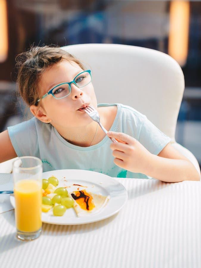 Vrolijk meisje die pannekoeken, verse vruchten en het drinken jus d'orange eten tijdens ontbijt Gezonde Levensstijl, Vegetarisch  stock afbeeldingen