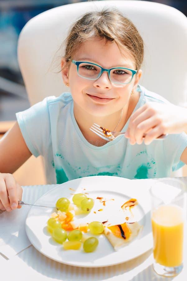 Vrolijk meisje die pannekoeken, verse vruchten en het drinken jus d'orange eten tijdens ontbijt Gezonde Levensstijl, Vegetarisch  stock foto