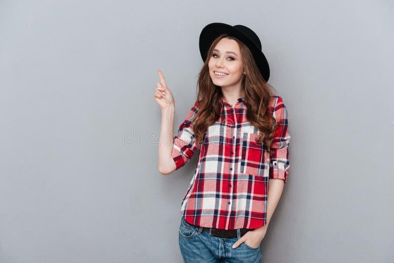 Vrolijk meisje die in plaidoverhemd vinger benadrukken op copyspace royalty-vrije stock afbeelding