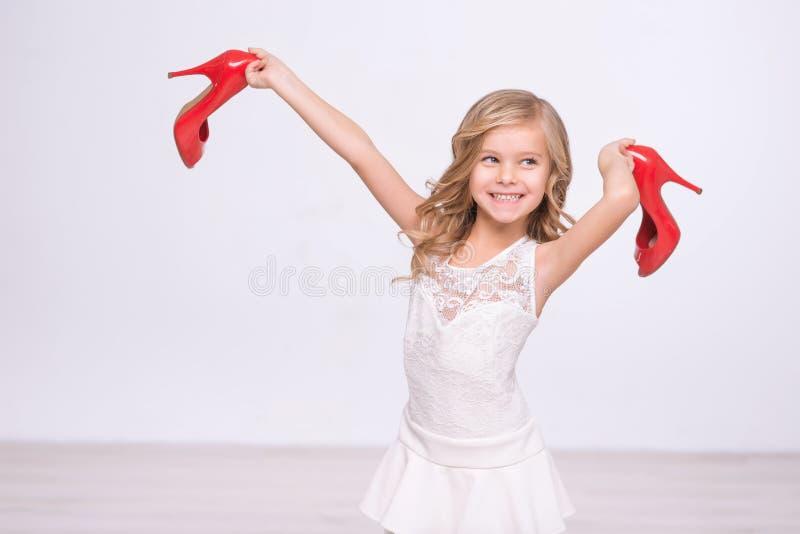 Vrolijk meisje die rode schoenen houden royalty-vrije stock fotografie