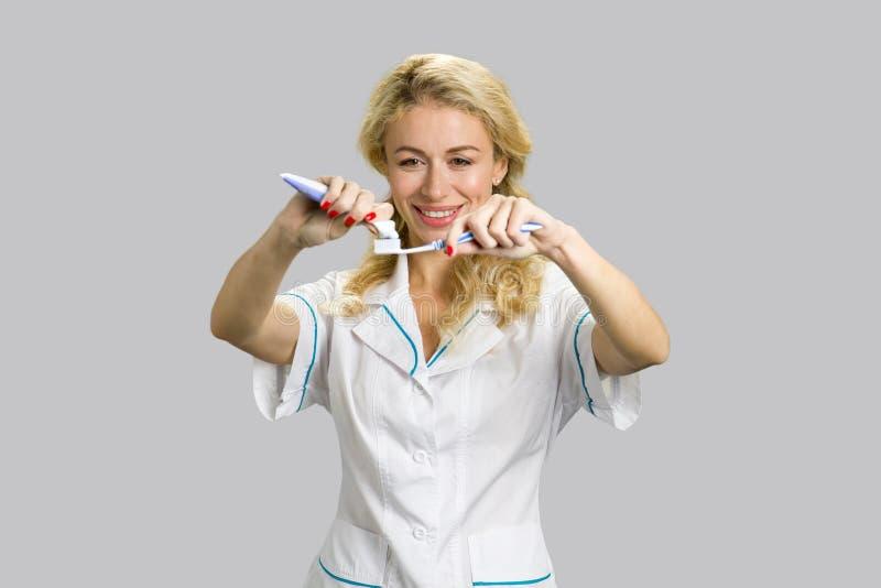 Vrolijk meisje die tandpasta op tandenborstel toepassen stock afbeeldingen