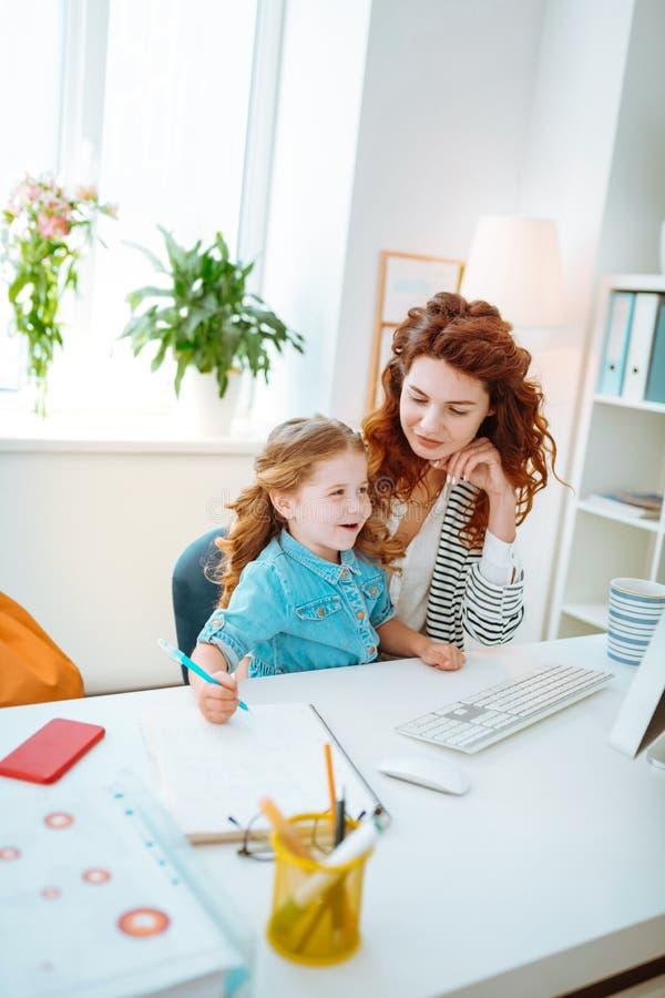 Vrolijk meisje die terwijl zich het aansluiten van bij moeder die aan computer werken schilderen royalty-vrije stock afbeelding