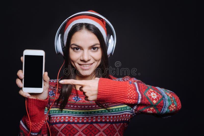 Vrolijk meisje die verschillende gadgets tonen aan het publiek stock fotografie