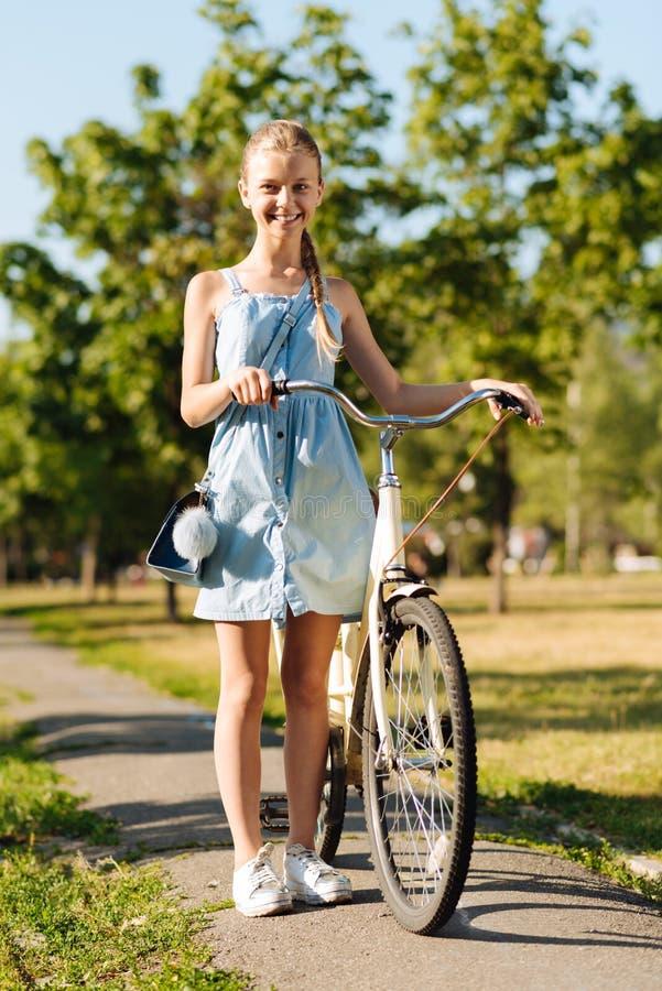Vrolijk meisje die zich dichtbij haar fiets bevinden stock foto