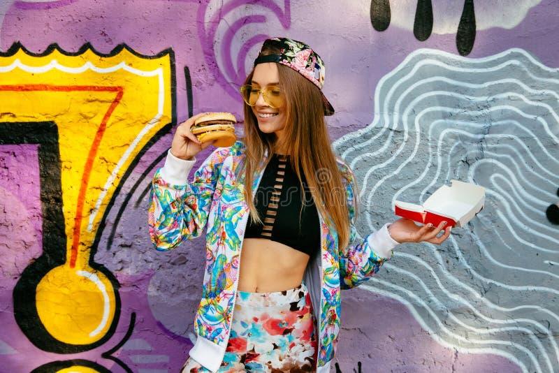 Vrolijk meisje een cheeseburger houden die zich bevindt dichtbij graffitimuur royalty-vrije stock foto