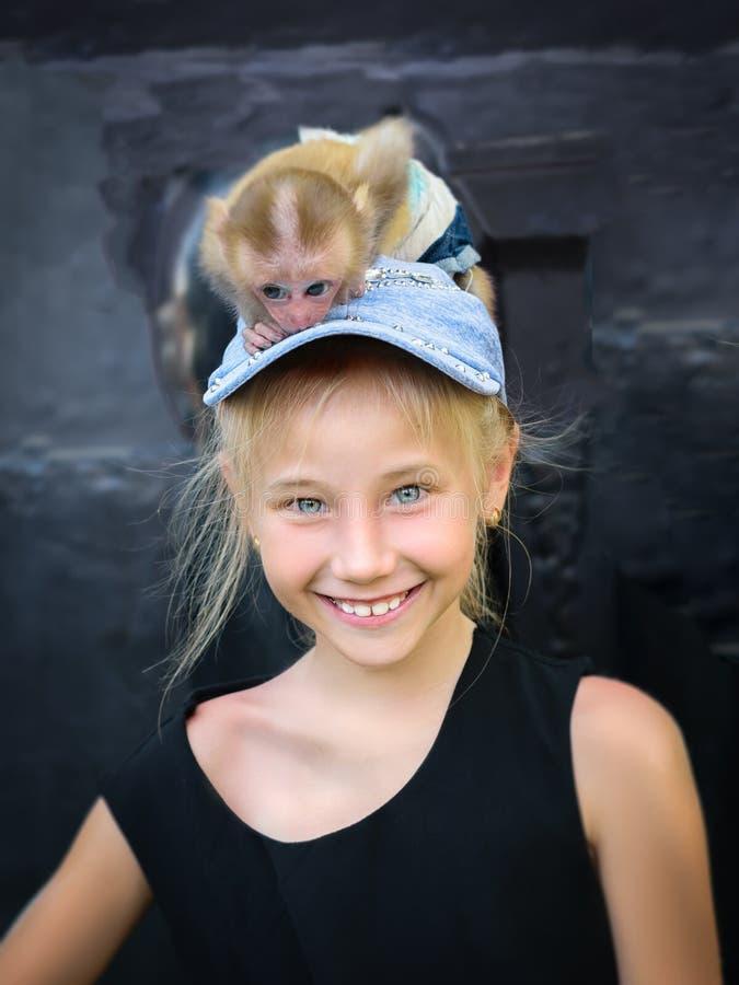 Vrolijk meisje in een denim GLB met een aap op haar hoofd stock foto's