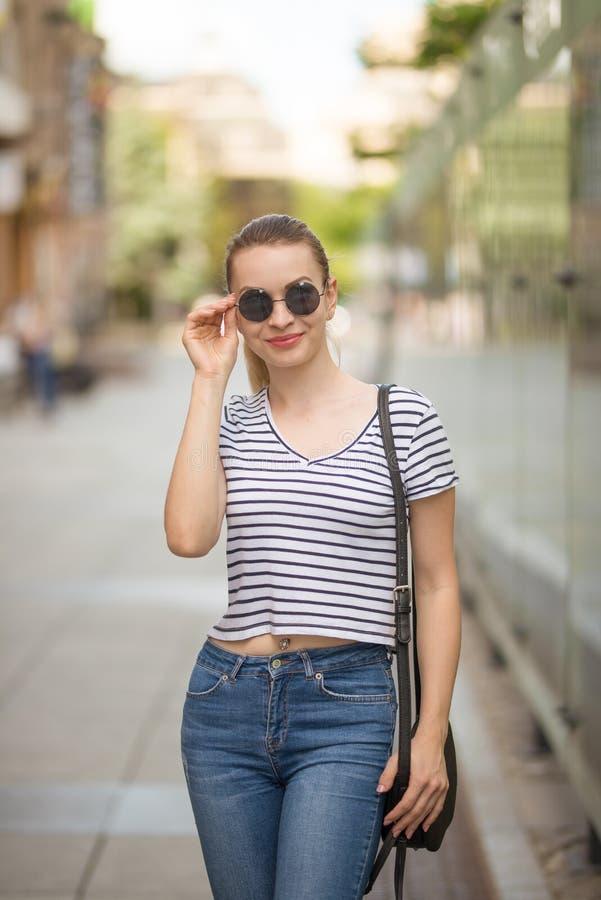 Vrolijk meisje hipster in glazen in stad het lopen royalty-vrije stock afbeeldingen