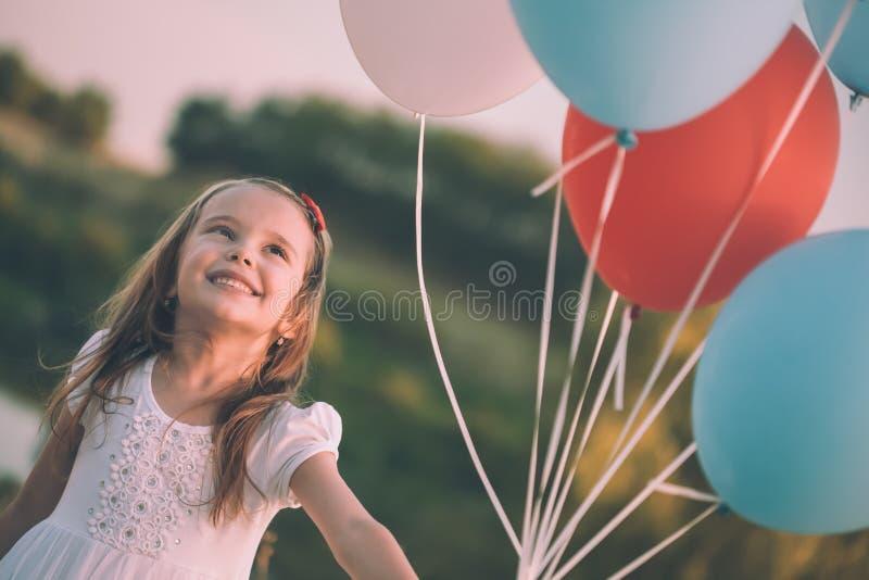 Vrolijk meisje met ballons op het gebied royalty-vrije stock afbeelding