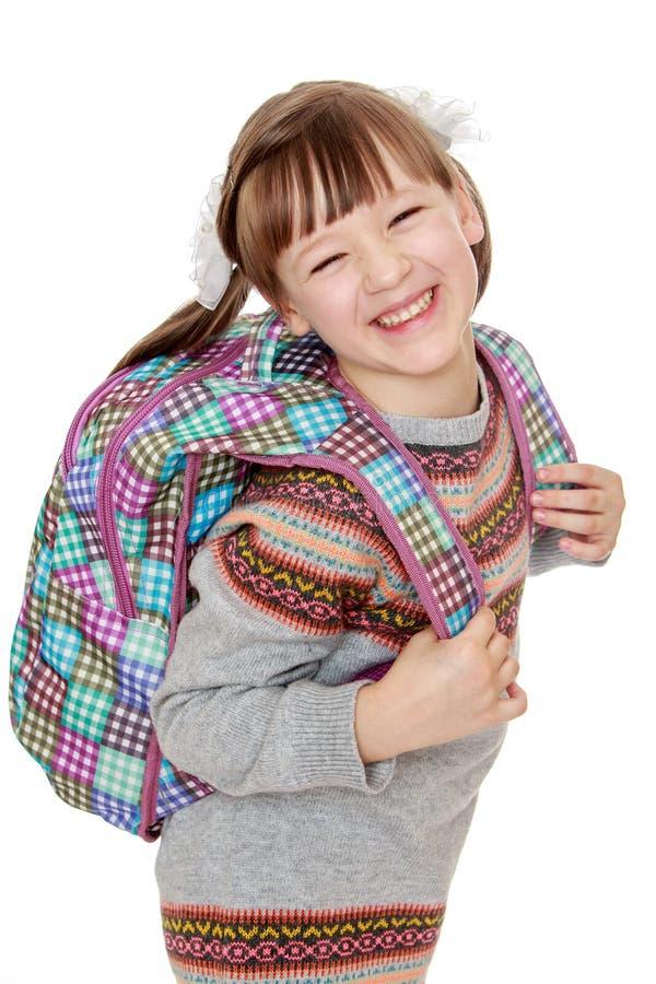Vrolijk meisje met een rugzak op zijn rug stock afbeelding