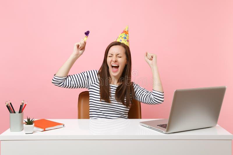 Vrolijk meisje met gesloten ogen in de hoed van de verjaardagspartij met het spelen van pijp het gillen het vieren terwijl het we stock afbeeldingen