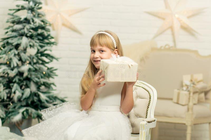 Vrolijk meisje met giften op de achtergrond van een Kerstboom in een witte ruimte royalty-vrije stock foto's