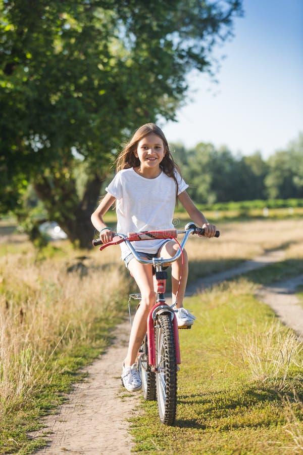 Vrolijk meisje met lang haar die haar fiets berijden bij de landweg bij stock foto