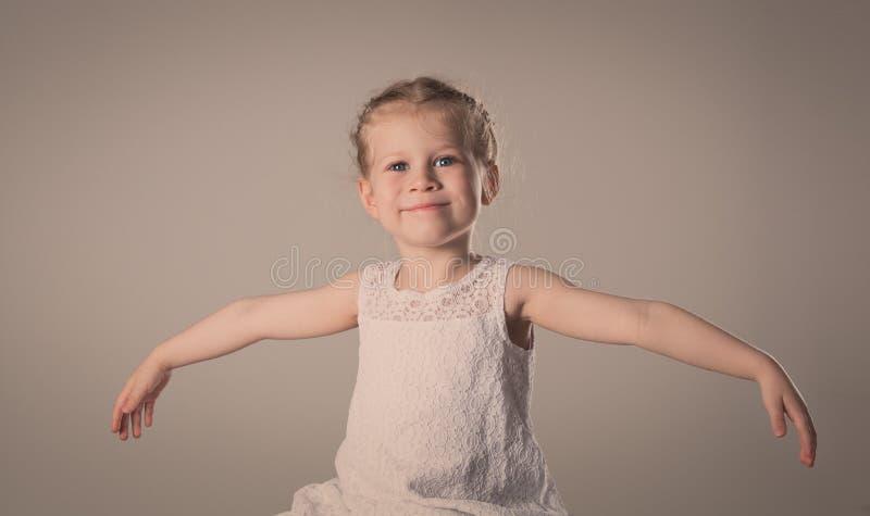 Vrolijk meisje met omhoog handen Gelukkig het glimlachen kindmodel stock afbeeldingen