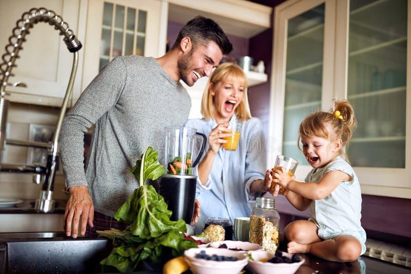 Vrolijk meisje met ouders in keuken royalty-vrije stock afbeelding