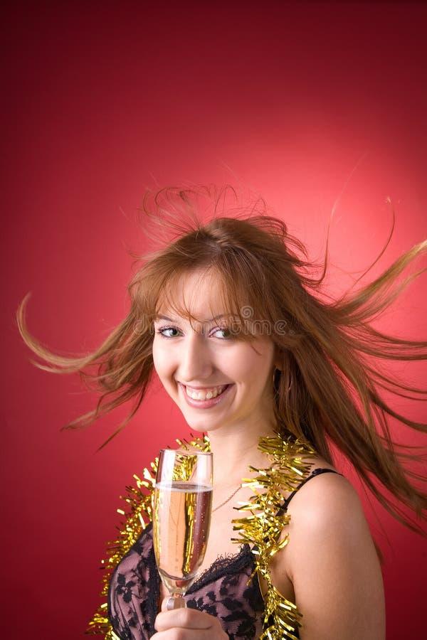Vrolijk meisje met vliegend haar en champagneglas stock foto's