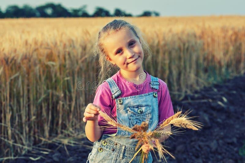 Vrolijk meisje op een gang dichtbij het gebied met tarwe royalty-vrije stock foto's