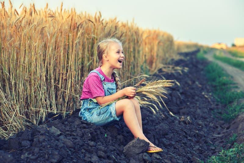 Vrolijk meisje op een gang dichtbij het gebied met tarwe stock afbeeldingen
