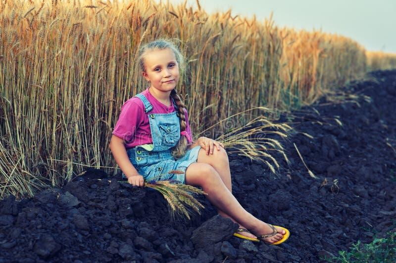 Vrolijk meisje op een gang dichtbij het gebied met tarwe royalty-vrije stock afbeeldingen
