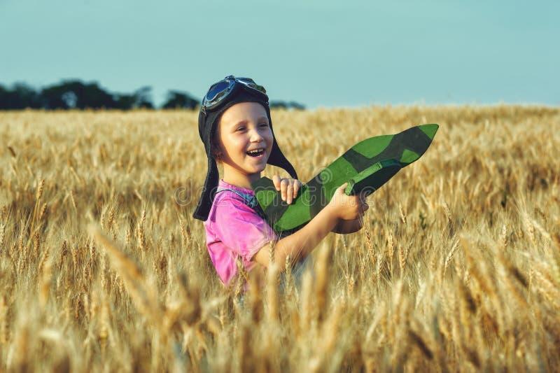 Vrolijk meisje op een gebied van tarwe het spelen met een modelvliegtuig royalty-vrije stock afbeelding