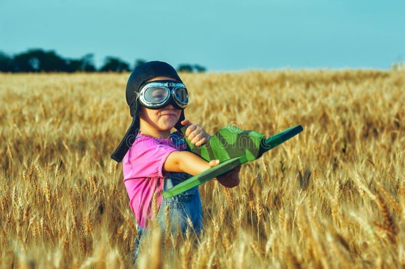 Vrolijk meisje op een gebied van tarwe het spelen met een modelvliegtuig stock afbeeldingen