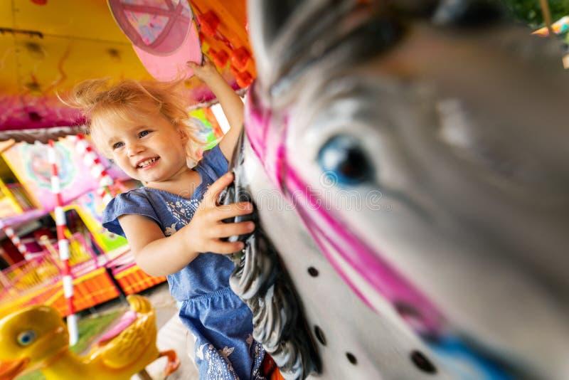 Vrolijk meisje op een paardcarrousel bij pretpark stock foto