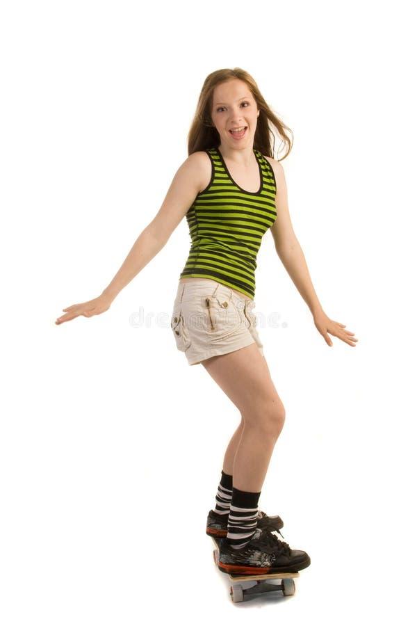 Vrolijk meisje op het skateboard stock foto