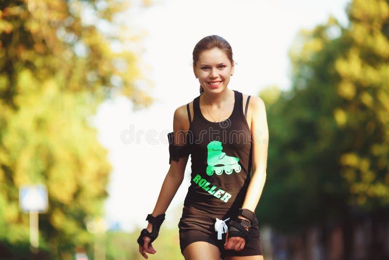 Vrolijk meisje op rolschaatsen stock afbeeldingen