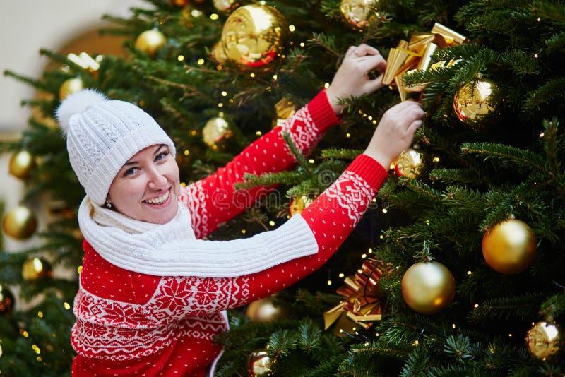 Vrolijk meisje in rode de wintersweater dichtbij Kerstboom royalty-vrije stock afbeelding
