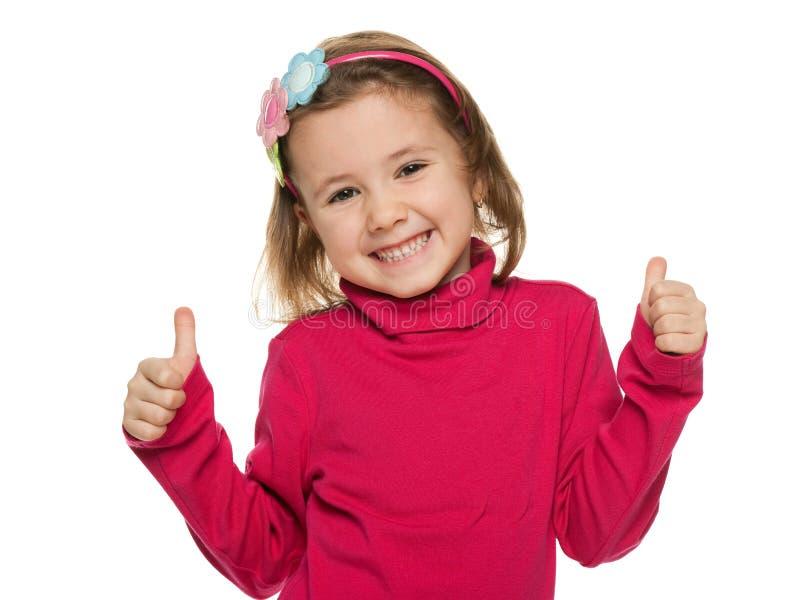 Vrolijk meisje in rood met haar omhoog duimen stock afbeeldingen